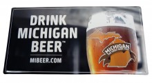 "Tin Tacker, 18"" x 9"" alumiuim featuring the full color ""DRINK MICHIGAN BEER"" logo. Each corner is rounded with a hole for hanging."